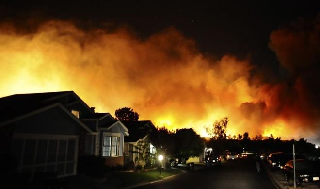 Incêndio é visto atrás de um conjunto residencial em Sylmar, na Califórnia: pelos menos duas pessoas morreram | Gene Blevins/Reuters