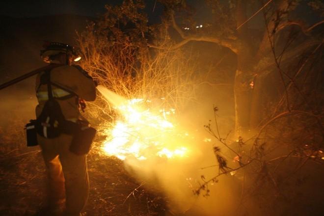Bombeiro apaga foco de incêndio: três focos já queimaram 88 quilômetros quadrados no sul da Califórnia | Mario Anzuoni / Reuters