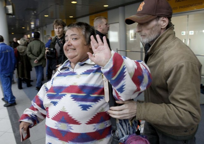 Passageira sai sorridente de avião, em São Petersburgo, após ameaça de bomba de um bêbado | Alexander Demianchuk / Reuters