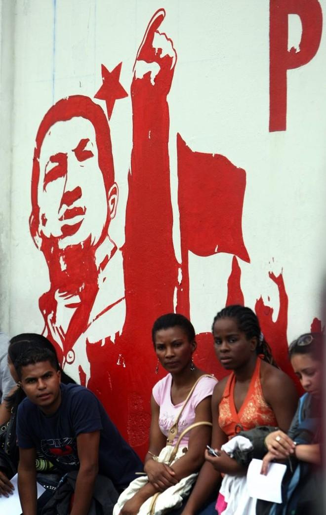 Moradores de Caracas esperam ônibus em frente de painel com propaganda chavista: projeto de socialismo do século 21 será avaliado nas urnas   Thomas Coex/AFP