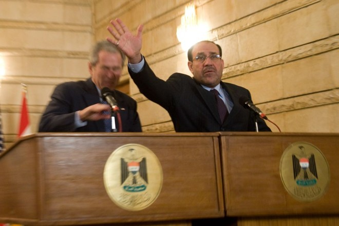 O primeiro-ministro iraquiano, Nuri al-Maliki, tenta proteger Bush dos sapatos | Saul Loeb/AFP