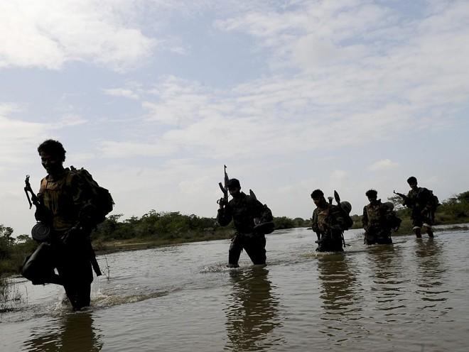 Soldados do Sri Lanka caminham num lago na recente captura da capital do país no território de Paranthan   Stringer / Reuters