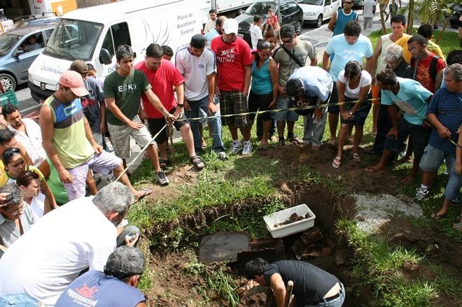 Curiosos acompanham a remoção da urna encontrada em Paranaguá, abaixo do obelisco que homenageia Júlia da Costa. | Divulgação