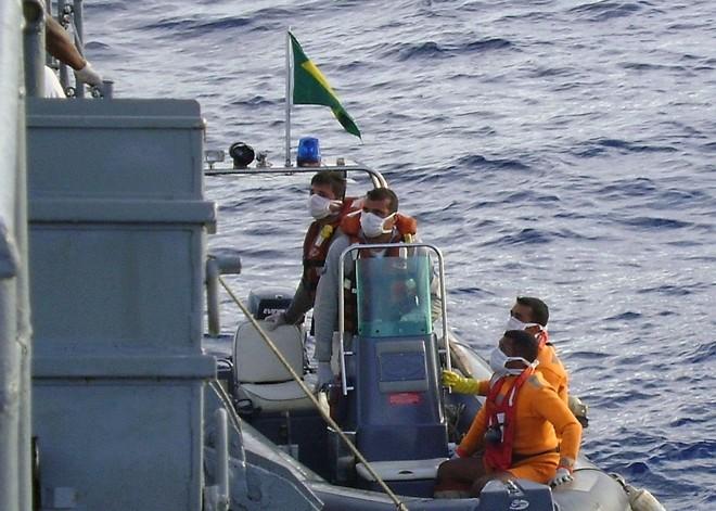 Integrantes das forças armadas voltam para um dos navios brasileiros após coletar destroços no mar | Reuters