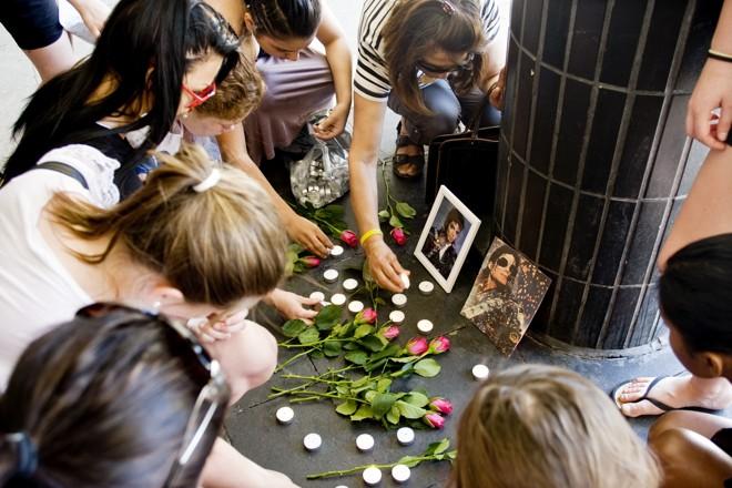 Meninas suecas colocam flores e velas em memória do falecido ícone pop dos EUA Michael Jackson na praça de Sergel no centro de Estocolmo |