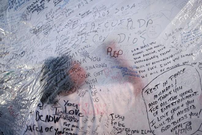 Fã assina seu nome mural no memorial público destinado ao astro pop morto Michael Jackson, no Teatro Apollo em Nova Iorque |