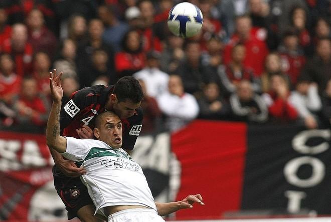 Rhodolfo ganha a disputa de bola com Ariel: enquanto o argentino saiu machucado, o atleticano tornou-se herói no segundo tempo | Rodolfo Bührer/Gazeta do Povo