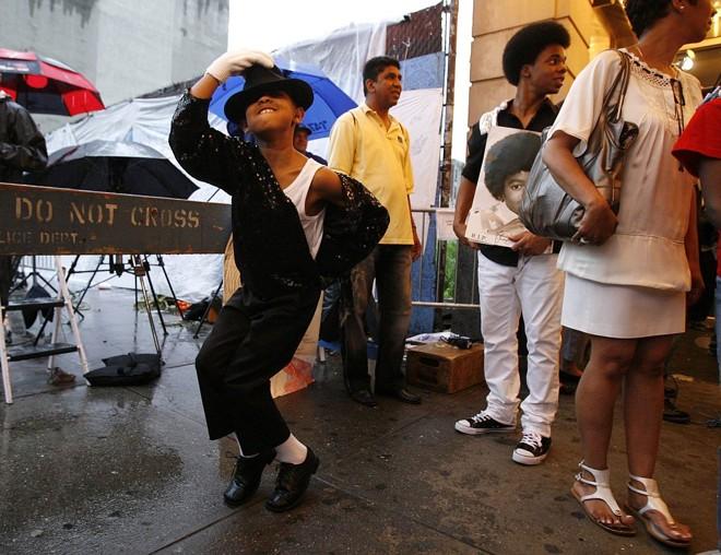 Menino ensaia passos do ídolo Michael Jackson na entrada do Teatro Apollo em Nova Iorque |
