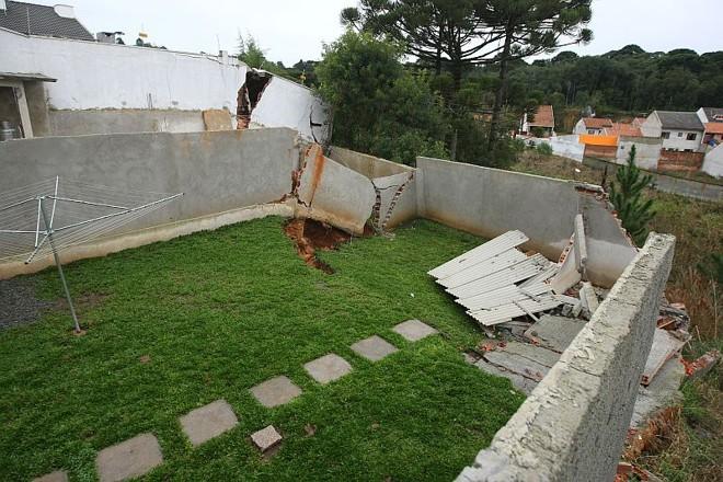 Fundos dos terrenos não suportaram o excesso de água e cederam. Churrasqueira, banheiro, canil e banheiro ficaram pendurados no barranco | Rodolfo Bührer/Gazeta do Povo