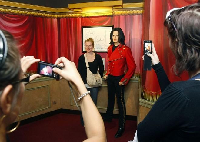 Visitantes posam para fotos ao lado do boneco de cera de Michael Jackson no Museu Grevin em Paris |
