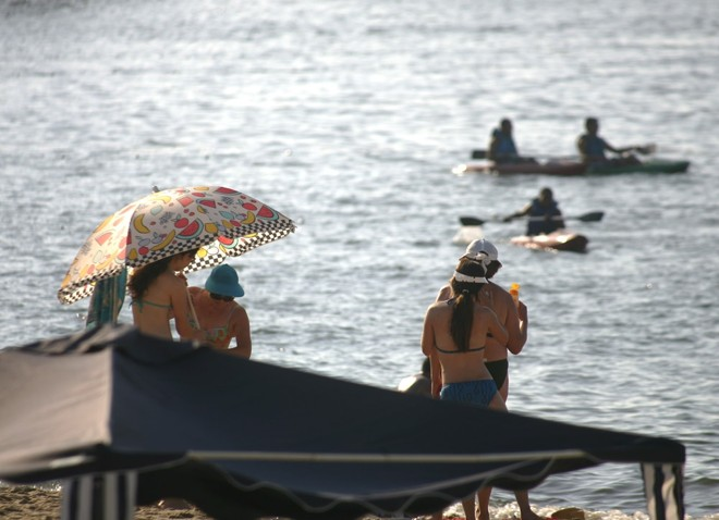 Veranistas aproveitam o dia quente para tomar sol e praticar esportes na água | Daniel Castellano/Gazeta do Povo