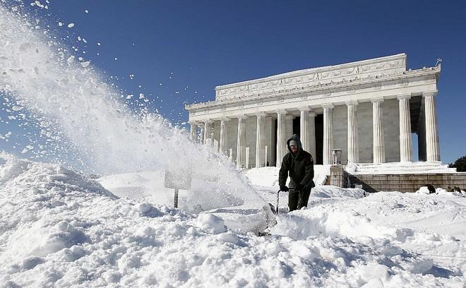 Trabalhador remove neve em frente ao Memorial Lincoln, em Washington   Reuters