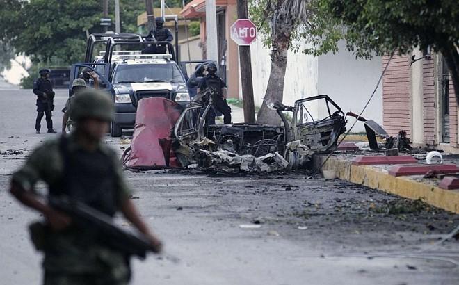 Policiais inspecionam o local onde uma das bombas explodiu, em Ciudad Victoria: intimidação | Henry Romero/Reuters
