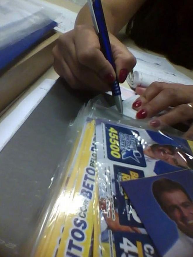 Funcionária entrega adesivos no gabinete de Felipe Braga Cortes | Reprodução