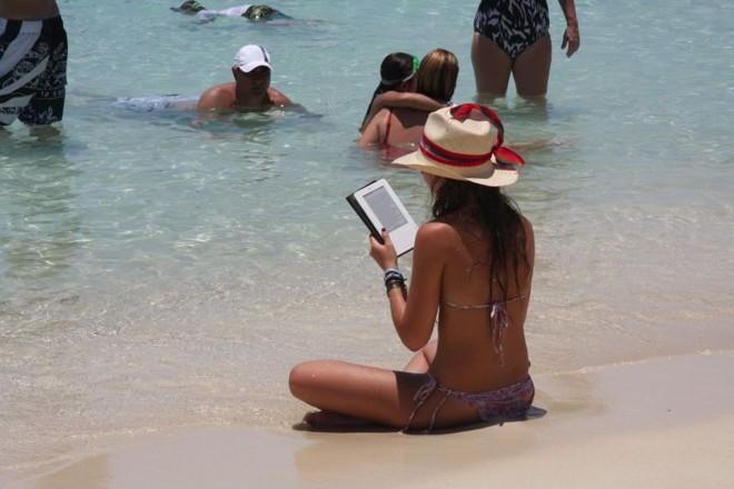 Banhista usa um leitor digital na beira do mar, com o sol a pino e os pés na água | Ricardo Medeiros / Gazeta do Povo