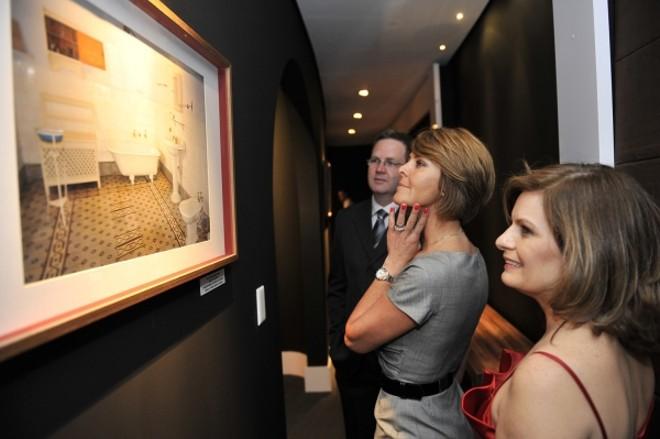 Acompanhada pelos anfitriões Léo Pletz e Francisca Cury, Fernanda Richa observa a exposição