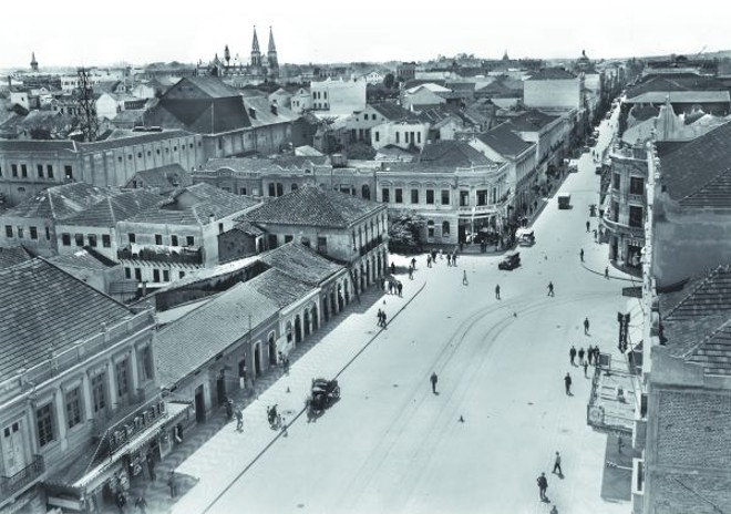 A fotografia é da Avenida Luiz Xavier e Rua Quinze de Novembro. Essa última ainda sendo mais estreita que a avenida. À esquerda, temos a torre dos Bombeiros; o telhado do Theatro Guayra se sobressai, e a Catedral aparece imponente na cidade rasa.  