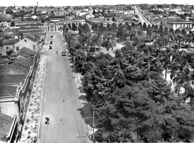 Agora a imagem mostra o mesmo lado Sul da Osório, vista do oitavo andar do Garcez. A vista se descortina em direção ao bairro do Batel ao fundo. Em primeiro plano, o viçoso arvoredo da praça – as árvores tinham 14 anos de idade. À direita, avista-se a Avenida Vicente Machado  