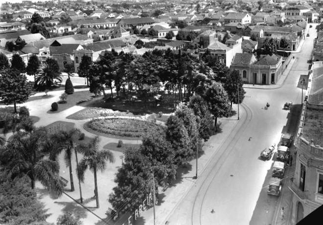 Outro canto da Praça Osório, com a Rua Voluntários da Pátria. O curitibano apelidou o conjunto de cedros que aparece na esquina como Bosque Vienense. Um tufão acabou com a poesia do bosque em 1940, derrubando todas as árvores  