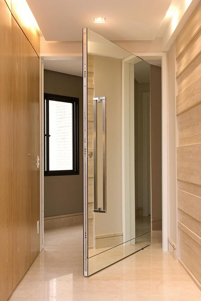 Destaque para o puxador vertical em aço inox na porta revestida de espelho, no projeto de Jorge Elmor. O espelho foi produzido pela MR Móveis |