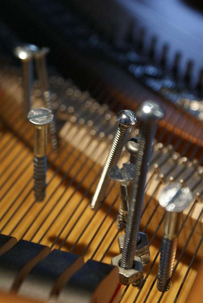 Parafusos pendem das cordas do piano |