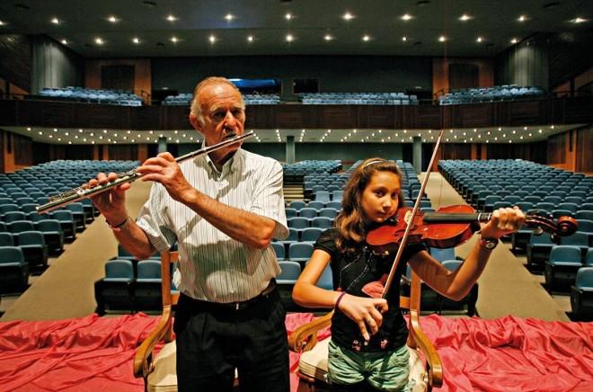 O flautista Elemar Schweizer, 72 anos, e a violinista Chiara Marella, 10: Orquestra de Câmara de Toledo reúne músicos de diferentes idades e classes sociais   Hugo Harada/ Gazeta do Povo