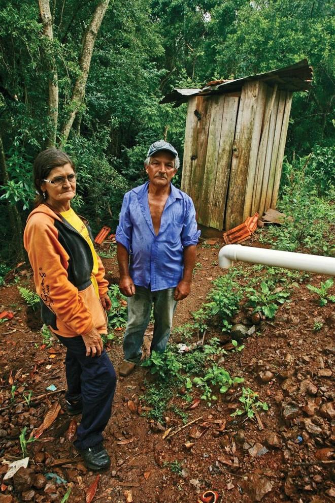 Geraldino e Alzira vivem em uma pequena casa de madeira sem banheiro. Eles têm de usar um vaso sanitário improvisado com um buraco cavado na terra   Hugo Harada/ Gazeta do Povo