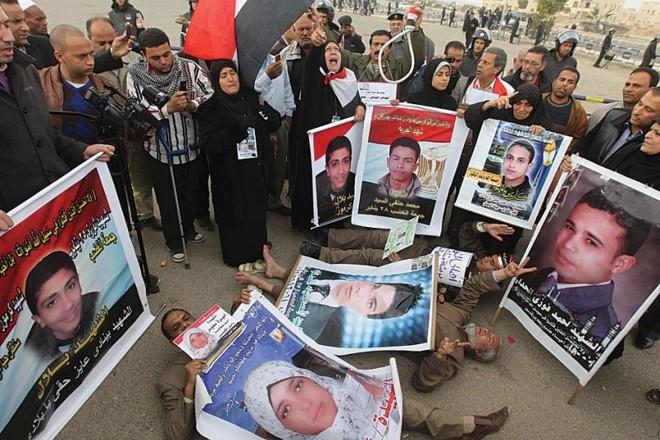 Manifestantes mostram fotos de vítimas que morreram nos protestos | AFP /Khaled Desouki
