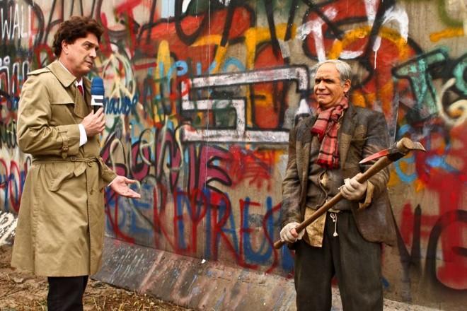Longa-metragem dá vida ao jornalista ficcional vivido por Hubert, que aqui divide a cena com Pedro Bial (à esq.) na cobertura da queda do Muro de Berlim, na  Alemanha | Davi de Almeida/Divulgação