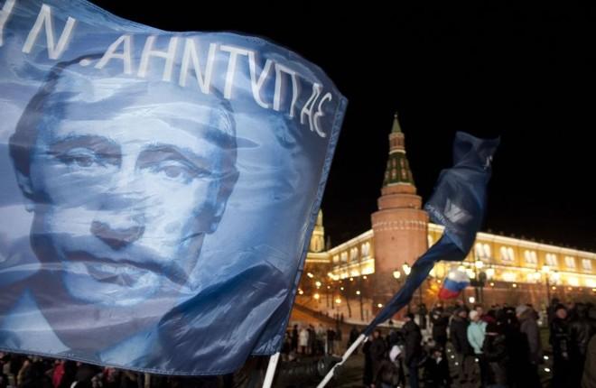 Partidário balança uma bandeira com o rosto de Putin | AFP