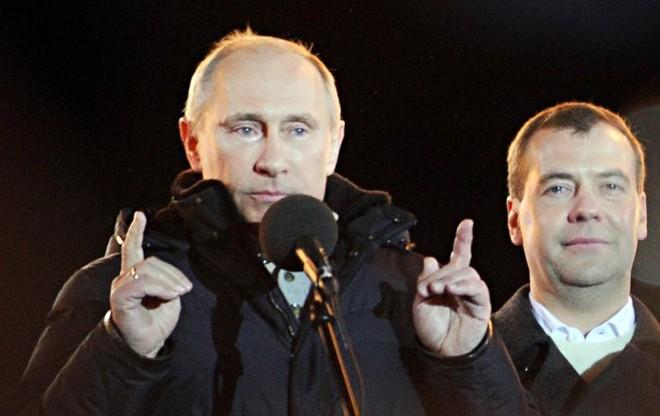 Com lágrimas nos olhos e ao lado do atual presidente Dmitry Medvedev, primeiro-ministro russo Vladimir Putin (esq.), acena para seus eleitores durante o pleito na praça Manezhnaya, em Moscou   Natalia Kolesnikova/AFP