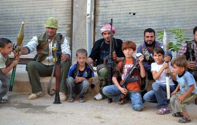 A agência oposicionista Shaam News divulgou imagens de soldados do Exército livre da Síria posando com armas e crianças na cidade de Kfar Nubul | Shaam News Network/Divulgação/AFP