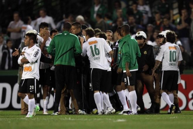 Após o término da partida, os jogadores do Coritiba cercaram o bandeira Émerson Augusto de Carvalho: queriam um impedimento que não ocorreu   Walter Alves/ Gazeta do Povo