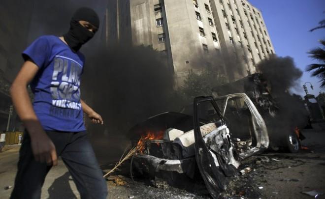 Manifestante passa por veículo destruído em uma das ruas que levam à embaixada dos EUA no Cairo, Egito | Reuters/Amr Abdallah Dalsh