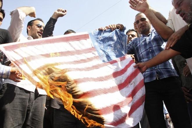 Manifestantes queimam a bandeira americana na cidade de Sadr, que fica a nordeste de Bagdá | Reuters/Wissm al-Okili