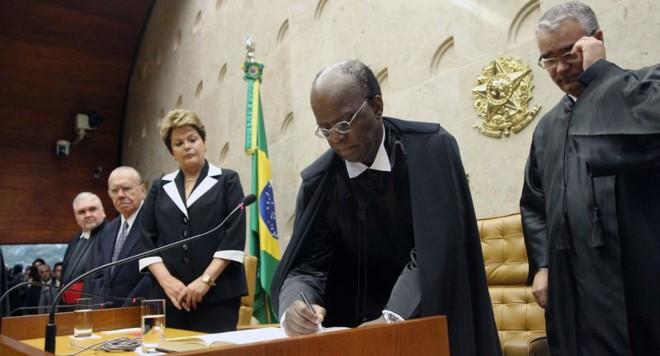 Joaquim Barbosa assina o termo de posse como presidente do Supremo, observado pela presidente: Dilma Rousseff não se curvou à ala do PT que queria que ela não fosse à posse   Carlos Humberto/STF