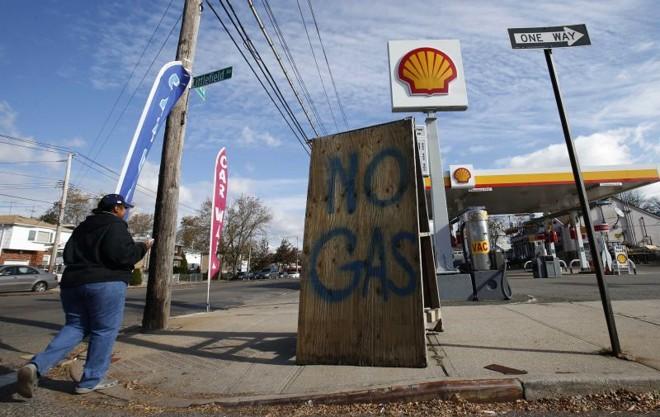Mulher caminha por posto com placa indicando que a gasolina acabou, em Staten Island | Mike Segar/Reuters