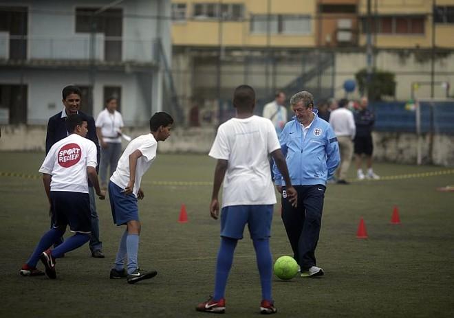Observado por Bebeto, o técnico da seleção inglesa, Roy Hodgson, bate bola com crianças do Instituto Bola Pra Frente, no Rio | Ricardo Moraes / Reuters