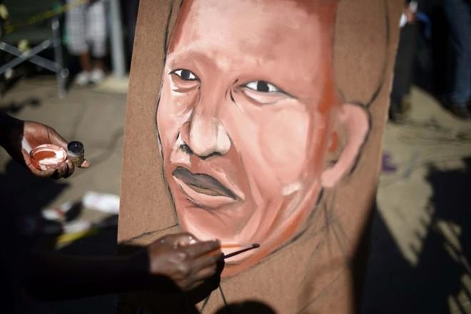 Homem pinta retrato do ex-presidente sul-africano Nelson Mandela, em Pretória | Dylan Martinez/Reuters