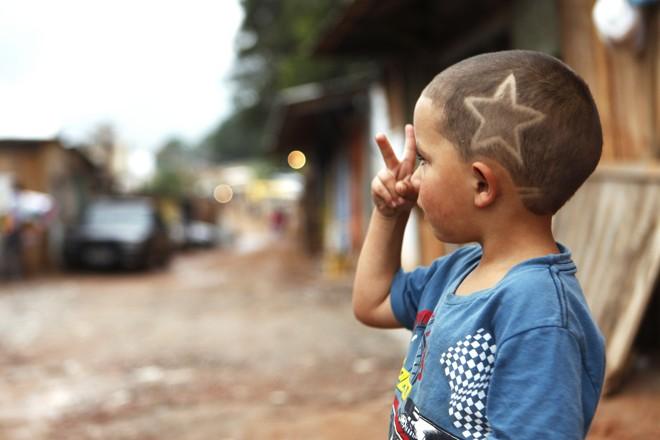 Garotinho exibe o novo corte de cabelo, na Ocupação Primavera |