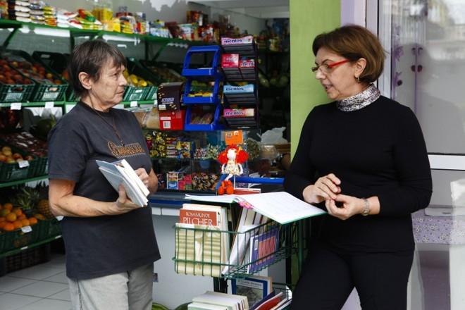 Luiza (à dir.) e o Carrinho de Leitura: ideia simples leva livros a moradores como Scheila Fonseca | André Rodrigues/Gazeta do Povo