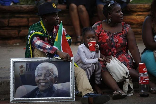 Casal segura retrato de Nelson Mandela próximo ao local onde o corpo do líder sul-africano é velado em Pretória | REUTERS/Mike Hutchings