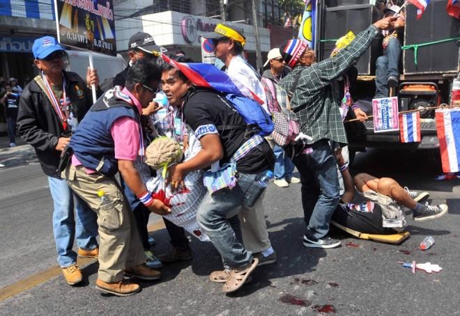 Manifestantes socorrem colega ferido por explosão   Stringer/Reuters