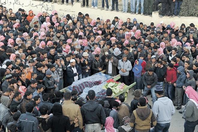 Libaneses rezam ao lado dos corpos de vítimas de um ataque sírio na cidade de Arsal | Hassan Abdallah/Reuters