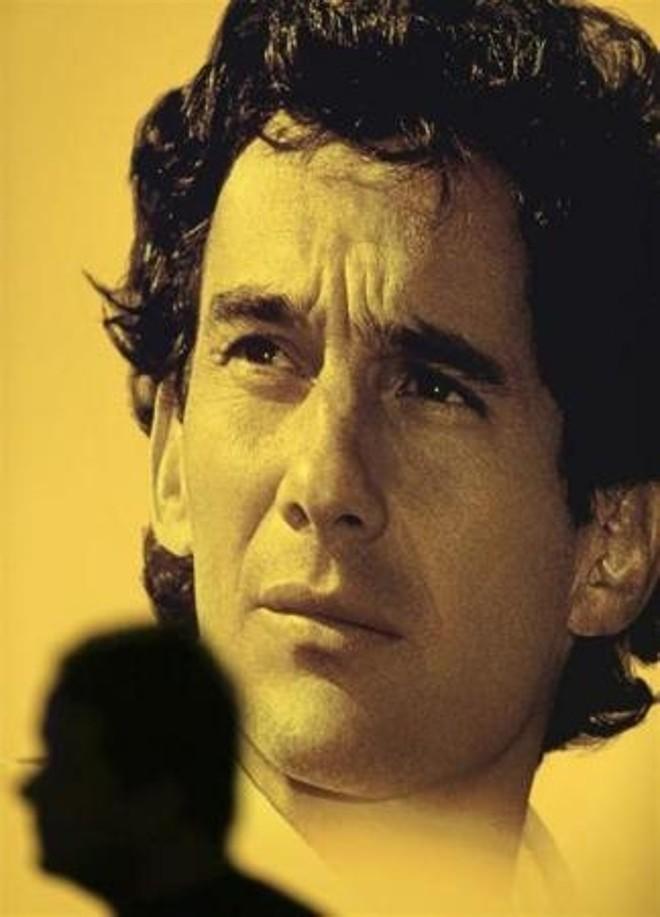 Uma pessoa passa na frente de uma imagem do piloto Ayrton Senna durante um evento em sua memória em São Paulo. | Reuters-Paulo Whitaker