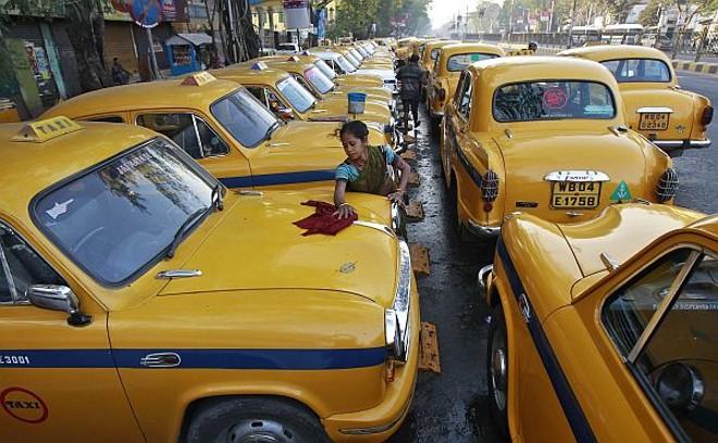 Sumitra Sarkar, 35, limpa dez carros diariamente por 150 rúpias indianas. Na foto, ela limpa um táxi amarelo em Kolkata, Índia | REUTERS/Rupak De Chowdhuri