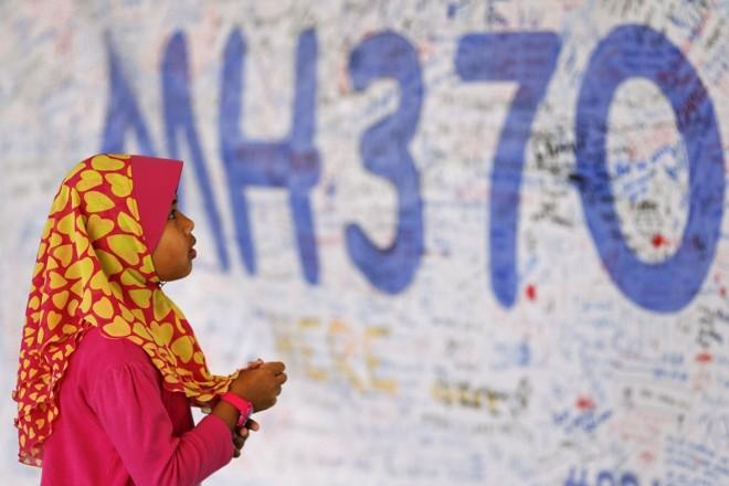 Menina observa um mural de mensagens em homenagem aos passageiros do voo 370 da Malaysia Airlines no aeroporto de Kuala Lumpur   Damir Sagolj/Reuters