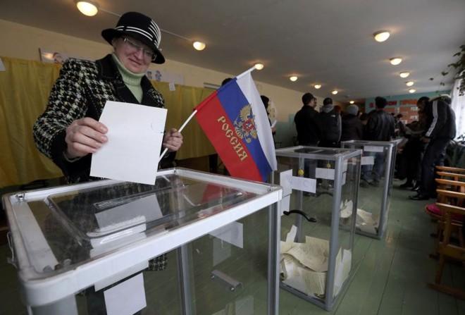 Mulher segura bandeira da Rússia ao depositar voto na urna no referendo sobre a anexação da Crimeia | REUTERS/Sergei Karpukhin
