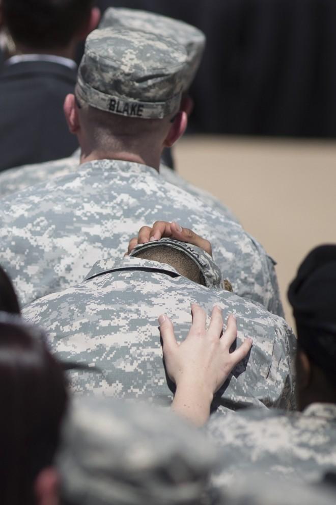 Homem é confortado por colega durante tributo | Julia Robinson/Reuters