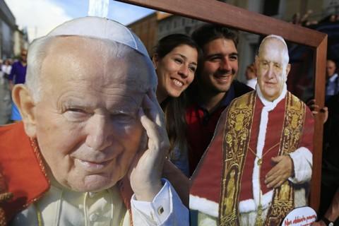 Fiéis fazem foto usando moldura com as imagens de João Paulo II e João XXIII, papas que serão santificados amanhã | Tony Gentile/Reuters